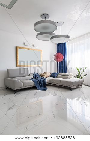 Modern room with white walls and light tiled floor. There are gray sofas with multicolored pillows and a blue plaid, fancy red lamp, hanging round lamps, plant in the pot, windows with curtains.