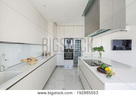 Stylish white kitchen with light tiled floor. There are lockers, tabletop with a sink, kitchen island with a stove and vegetables and kitchen hood, leaves in a vase, fridge with glass door, oven, TV.