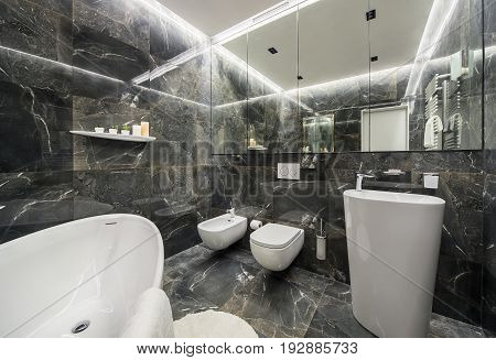 Modern bathroom with textured dark tiles and luminous lamps. There is a white bath, large mirror, toilet and a bidet, tall sink with a chrome faucet, shelf with plants in the pots and candles.