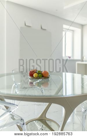 Round glass table with same chairs around it in the modern white interior with light tiled floor. There is a metal plate with fruit on the table. Closeup. Indoors. Vertical.