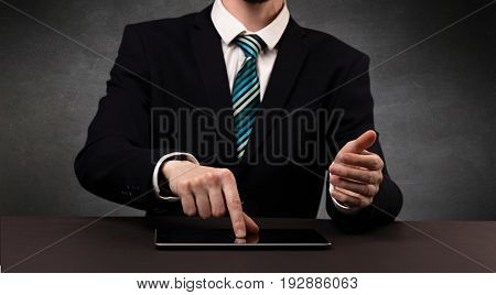 Businessman in suit typing with dark background