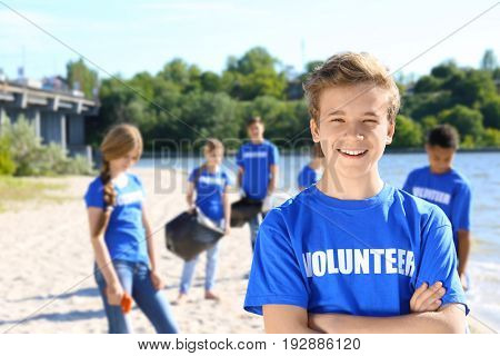 Young boy standing with crossed hands outdoors. Volunteer concept