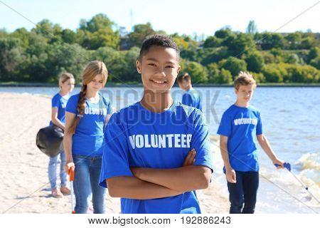 Young boy standing with crossed hands outdoor. Volunteer concept