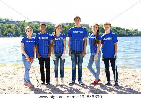 Young people with trash pickers standing on beach near river. Volunteer concept