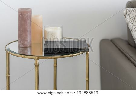 Stylish small round metal table with a glass top with candles and a book on it on the white wall background. There is gray sofa with a pillow near the table. Closeup. Indoors. Horizontal.