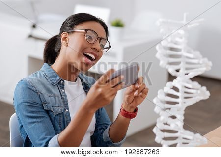 Interesting object. Positive delighted smart woman sitting at the table and holding her smartphone while taking a photo of a DNA model