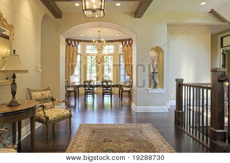 Grand foyer with area rug and view to dining room