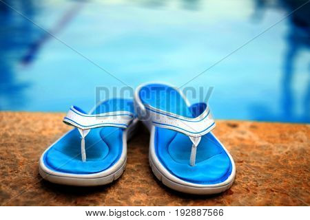 Pair of sandals flip flops next to clear swimming pool with blue water