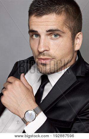 Portrait of a man with a light unshaven in a black suit wristwatch studio