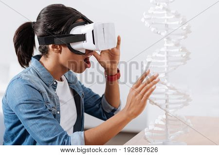 Scientific discovery. Nice smart young woman wearing 3d glasses and looking at the DNA model while doing a scientific discovery
