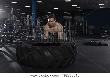 Muscular, Strong and fit man preparing to push tire in modern fitness center. Cross workout. Functional training