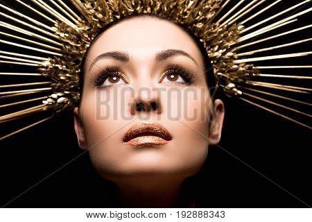 Close Up View Of Attractive Woman In Golden Headpiece Looking Up Isolated On Black