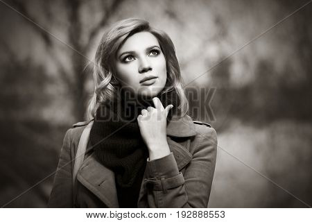 Young blond woman walking in autumn forest. Stylish fashion model outdoor