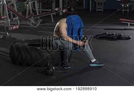 attractive muscular shirtless athlete taking the break from heavy training in modern fitness center. Functional training .Cross workout