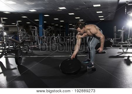 Male shirtless athlete preparing for barbell workout in gym. Functional training. Cross workout