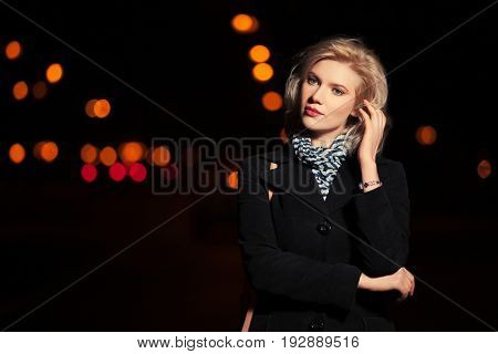 Sad young blond woman walking in a night city street. Stylish fashion model in black coat outdoor