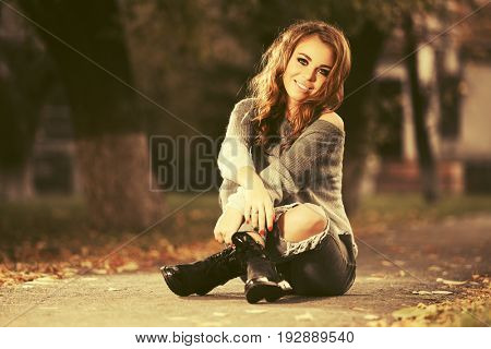 Happy young woman in ripped jeans sitting in city street. Stylish fashion model with long curly hairs outdoor