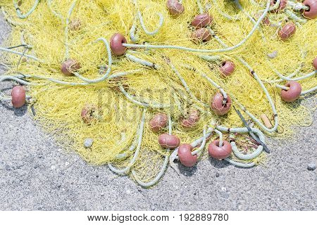 Yellow fishing net on the cement quay