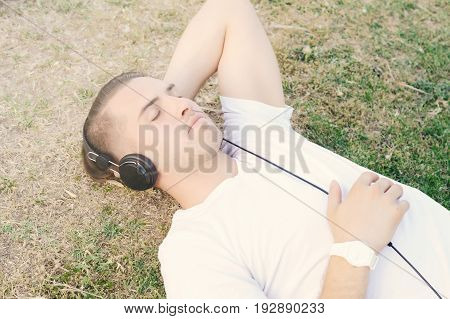Young attractive man listening to music with headphones in a park. Outdoors.