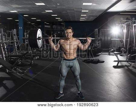 Attractive muscular shirtless athlete doing heavy  squat exercise in modern gym.Functional training.