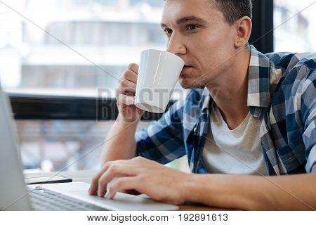 Take a sip. Hardworking industrious quick witted man having productive time while spending some time in the cafe and reading his mail