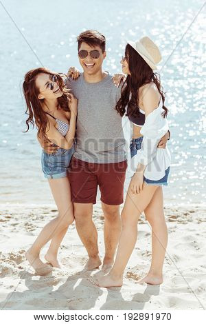 happy asian man hugging with two cheerful girls on sandy beach