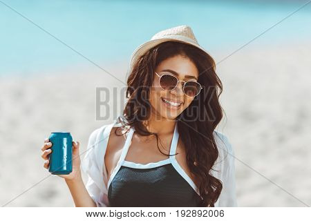 Beautiful young woman in sunglasses and straw hat holding soda can and smiling at camera