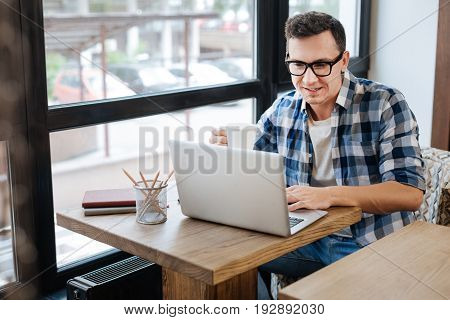 Academic spirits. Intelligent curious dedicated man developing a plan for his business while sitting in a cafe and enjoying morning coffee