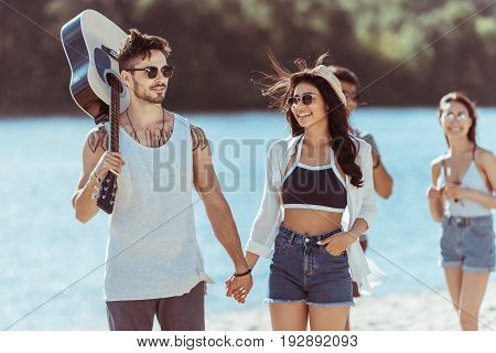 Happy Interracial Couple Holding Hands While Man Carrying Guitar On Riverside