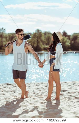 Happy Man Carrying Guitar And Holding Hands With His Girlfriend On Sandy Beach