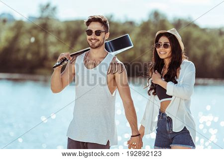 Smiling Interracial Couple In Sunglasses Holding Hands While Man Carrying Guitar