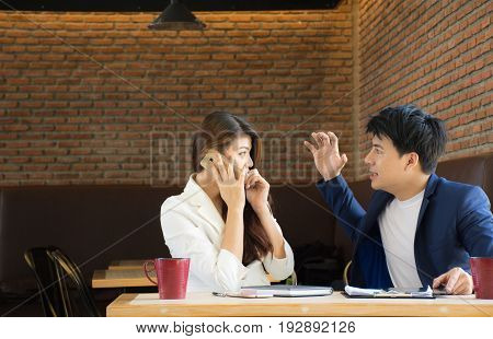 Angry man while women are talking on the phone In a cafe / Angry couple facing off during argument