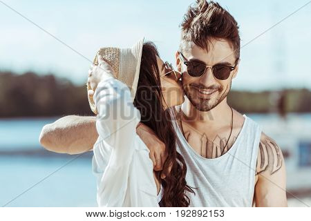 Happy Interracial Couple In Sunglasses Hugging While Girl Kissing Her Boyfriend