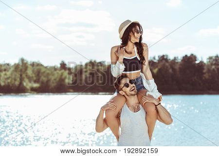 Attractive Woman Sitting On The Shoulders Of Smiling Man At Riverside