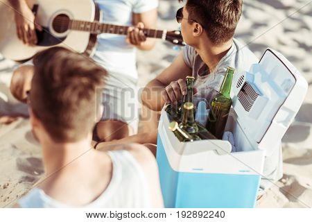 Young friends drinking beer and playing guitar while sitting together on beach