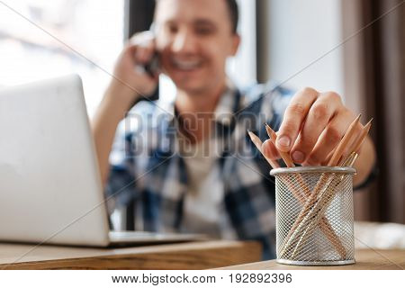 Writing tool. Inspired clever handsome man making some business calls and wanting putting down some notes while talking