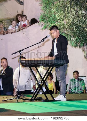 Nahariya Israel June 11 2017 : Singer performs a song accompanying himself on a keyboard instrument at the celebration of the city's day in Nahariya Israel