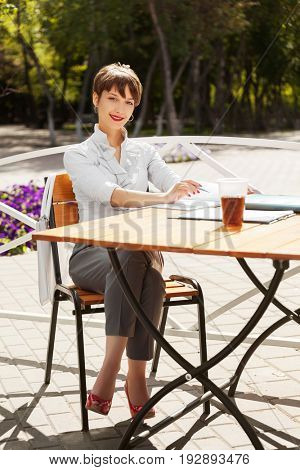 Happy young business woman working at sidewalk cafe. Stylish fashion female model in white blouse outdoor