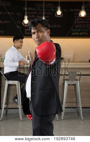 Managers are prepared to fight business problems,In a cafe/Determined businessman in suit and boxing gloves