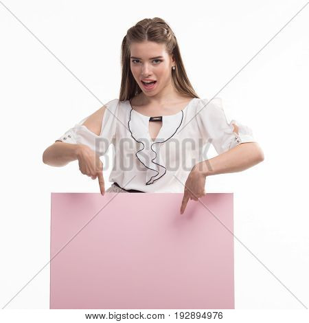 Young glad woman portrait of a confident businesswoman showing presentation, pointing paper placard pink background. Ideal for banners, registration forms, presentation, landings, presenting concept..