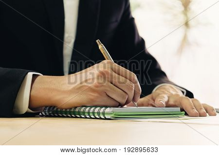 Close up of business man in shirt and suit working in his office writing in a classic notebook.