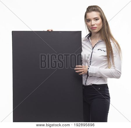 Young serious woman portrait of a confident businesswoman showing presentation, pointing placard black background. Ideal for banners, registration forms, presentation, landings, presenting concept..