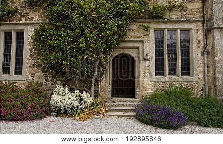 Part of a 19th century house showing the back door surrounded by plants