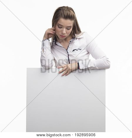 Young pry woman portrait of a confident businesswoman showing presentation, pointing placard gray background. Ideal for banners, registration forms, presentation, landings, presenting concept..