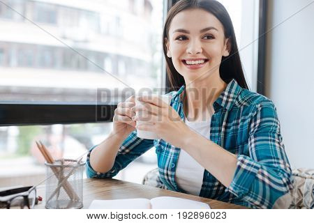 He will come soon. Positive emotional energetic lady sitting in a public place and enjoying some hot coffee while looking at the door