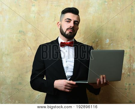 Stylish looking bearded businessman with confident face expression holds high tech laptop on light old painted background. Success and technology concept