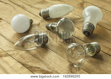 On a wooden surface are lamps with different cap
