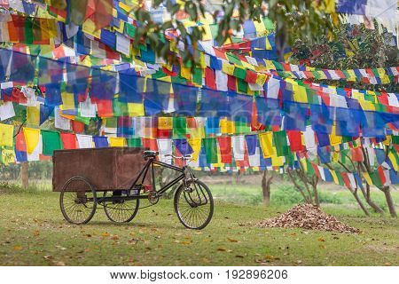 The rickshaw on the way to an enlightenment. Old tricycle - the rickshaw used for cargo hauling stands in the shadow of Buddhist prayful flags - Lungta hanging on the territory of the temple complex of mother of Buddha - Maya Devi in Lumbini Nepal.