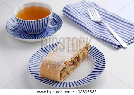 Slice of strudel under powdered sugar and a cup of tea