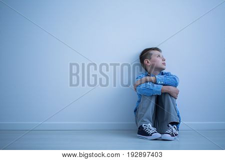 Sad lonely child sitting on a floor in an empty room